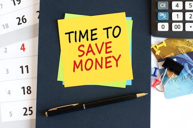 Tempo per risparmiare, testo su carta gialla a forma quadrata su sfondo blu. blocco note, calcolatrice, carte di credito, penna, cancelleria sul desktop. concetto di affari, finanziari e di istruzione.