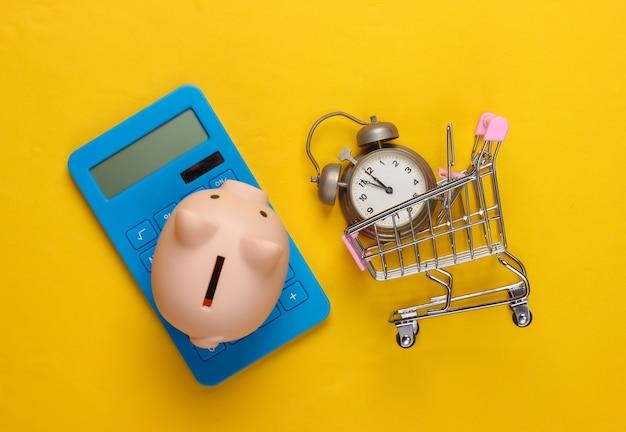 Tempo per lo shopping calcolatrice, salvadanaio, carrello del supermercato con sveglia su giallo