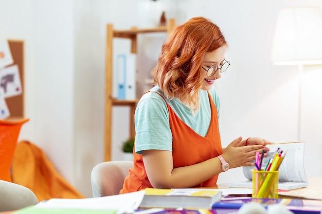 Tempo di studiare. donna dai capelli rossi positiva che apre un libro mentre è pronta per studiare