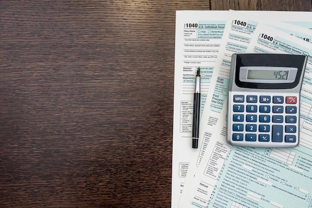 Tempo per le tasse, modulo federale con penna e calcolatrice, scrivania da ufficio