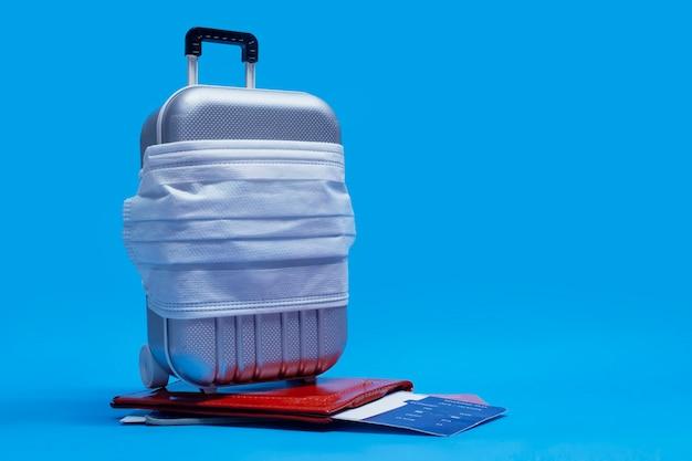È ora di viaggiare. cancellazione del volo e concetto di riposo sicuro durante una pandemia di coronavirus covid-19. valigia per viaggiare con mascherina medica e biglietti aerei con passaporto.