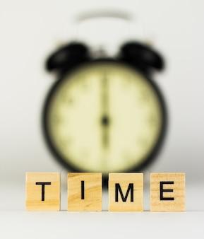 Parola di tempo nel cubo di legno con sveglia sfocata