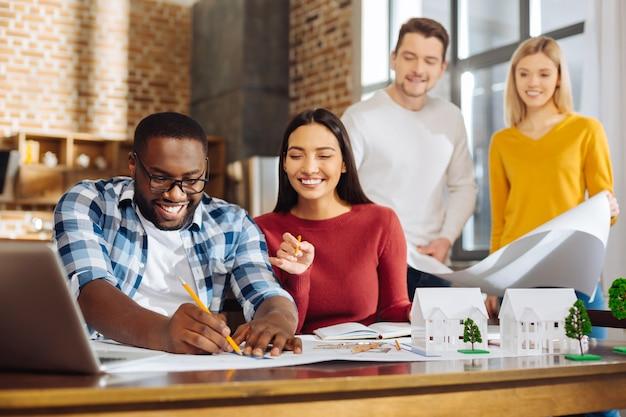Tempo di lavorare . gruppo di giovani colleghi graziosi allegri che discutono del progetto mentre ridono e lavorano insieme