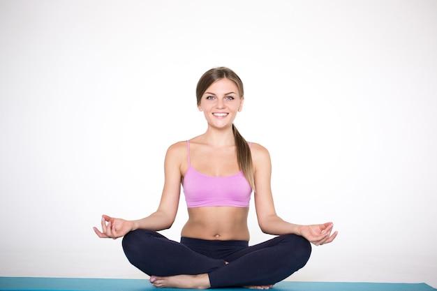 Tempo per lo yoga. giovane donna che si esercita e che si siede nella posizione del loto di yoga.