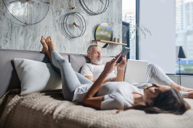 Tempo per te stesso. uomo barbuto adulto serio e giovane donna con gadget comodamente seduti a casa sul letto