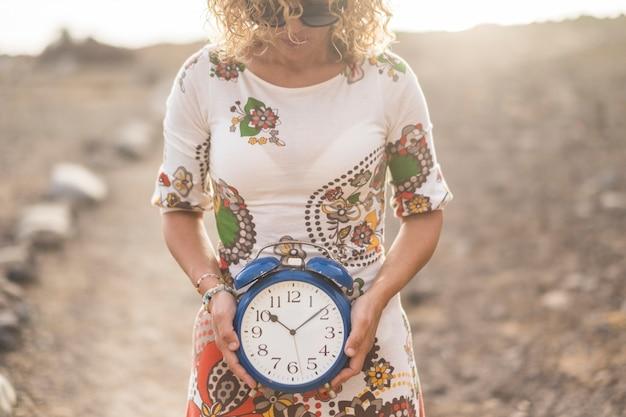 Concetto senza tempo e tempo con una bella donna che prende una grande sveglia blu vintage e ti mostra i minuti che se ne vanno. vivi e goditi il concetto. sole in controluce e all'aperto