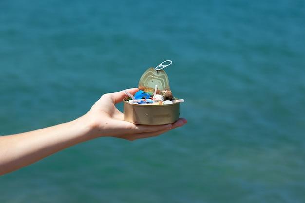 Il barattolo di latta in mano femminile sullo sfondo del mare è pieno di rifiuti di plastica e immondizia