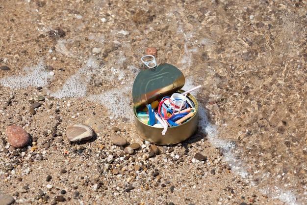 Barattolo di latta riempito fino all'orlo con rifiuti di plastica raccolti sulla spiaggia inquinamento del mare con microplastica