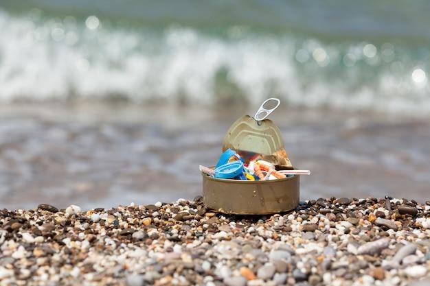 Barattolo di latta pieno di immondizia di plastica raccolta sulla spiaggia. concetto: consumo eccessivo di imballaggi usa e getta, inquinamento degli oceani del mondo con microplastiche.
