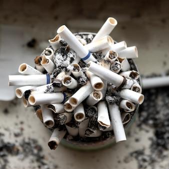 Barattolo di latta pieno di sigarette fumate in piedi sul davanzale. vista dall'alto