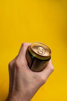 Barattolo di latta nella mano di un uomo su uno sfondo giallo