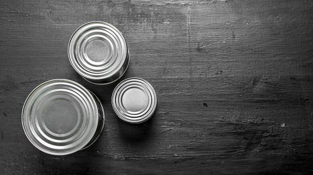 Barattoli di latta con il cibo sulla lavagna nera