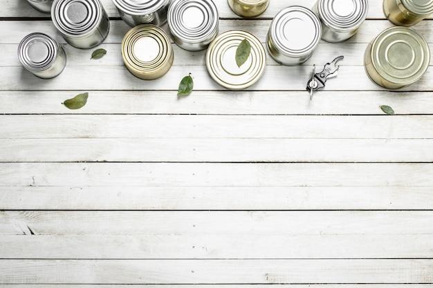 Barattoli di latta con cibo e apriscatole. su un tavolo di legno bianco.
