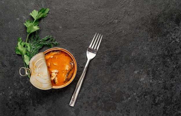 Tulka in scatola in pomodoro in un barattolo di latta con una forchetta su uno sfondo di pietra con copia spazio per il testo