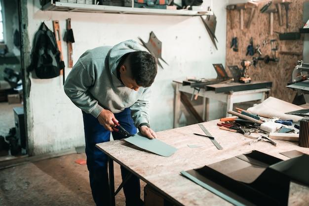 Il fabbro di lattoniera usa il martello che lavora nella sua officina. laboratorio di fabbri. giovane lattoniere nella sua bottega.