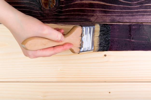 Tingere il legno con un pennello. vista dall'alto, primo piano.