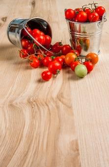 Pomodori minuscoli del bambino in un piccolo secchio su una tavola di legno. copia spazio