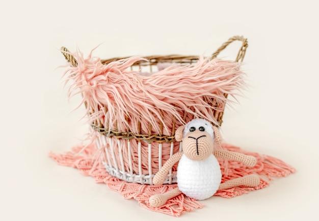 Piccolo cesto decorato per il servizio fotografico in studio neonato pieno di pelliccia e primo piano giocattolo lavorato a maglia. mobili fatti a mano per neonati