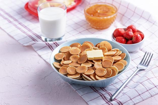 Frittelle di cereali minuscole con fetta di burro, fragole, miele e bicchiere di latte su bianco
