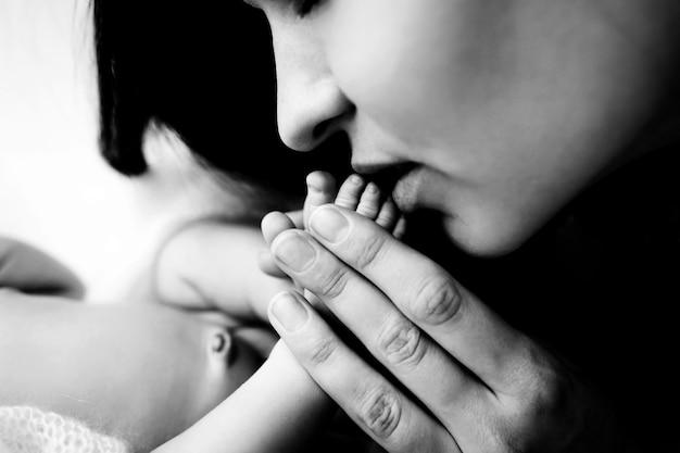 Piccoli piedi di un neonato nelle mani di un genitore. bambino di una settimana. l'immagine dei primi giorni di vita. immagine del concetto di famiglia felice, maternità e infanzia felice. foto di alta qualità