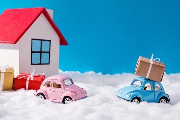 Piccole auto rosa e blu e regali di natale