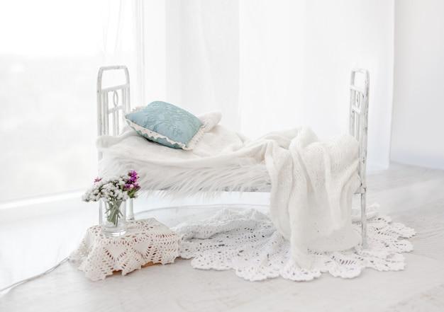 Piccolo arredamento da letto bianco per il servizio fotografico in studio neonato con coperta a maglia in primo piano. mobili per foto per neonati