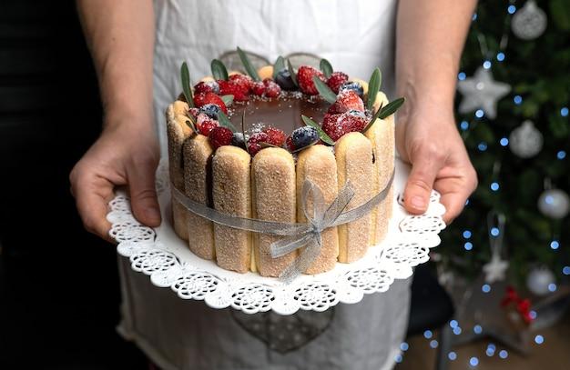 Tiramisù ricoperto di glassa al cioccolato e decorato con frutti di bosco