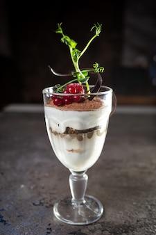 Dessert di tiramisù in un bicchiere con frutti di bosco. bella porzione del piatto