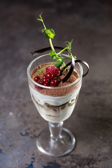 Dessert di tiramisù in un bicchiere con frutti di bosco.