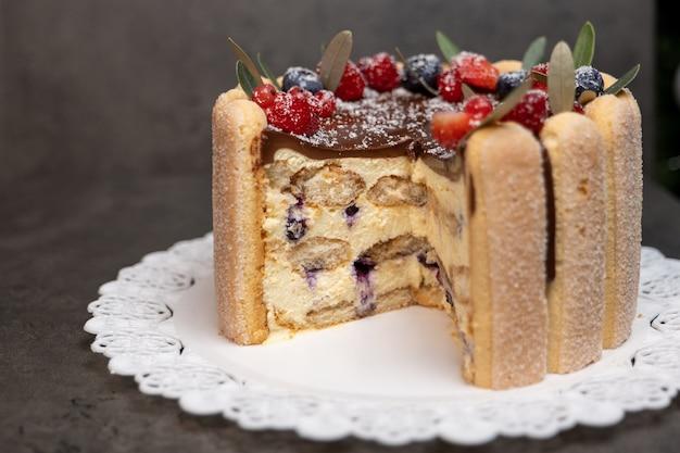 Tiramisù condito con glassa al cioccolato e decorato con frutti di bosco
