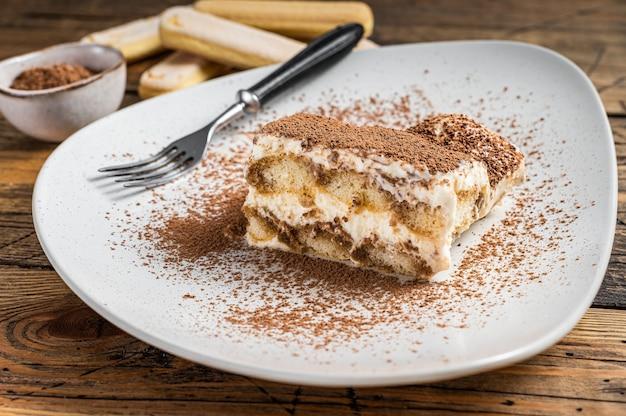 Tiramisù torta italiana con cacao in un piatto. fondo in legno. vista dall'alto.