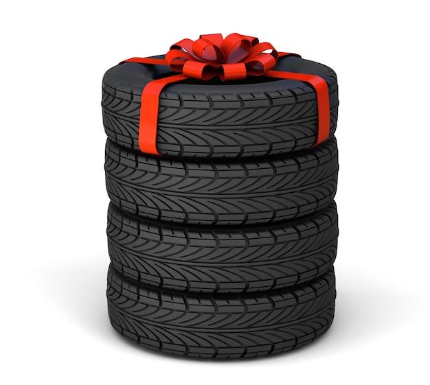 Pneumatico come regalo set di tre pneumatici uno legato con un nastro regalo rosso con un fiocco isolato su bianco