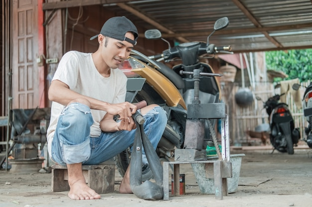 Riparatore di pneumatici seduto a strofinare una camera d'aria che perde in un'officina di riparazione di moto