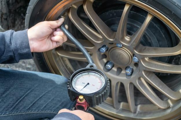 Manometro dei pneumatici e mani del tecnico che controllano la pressione dei pneumatici