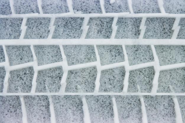 Un'impronta di pneumatico nella neve, una strada invernale in caso di maltempo.