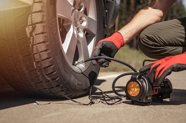 Pompa per pneumatici che gonfia il gonfiatore per pneumatici della ruota dell'auto nelle mani dell'uomo con manometro