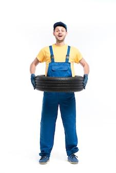 Servizio pneumatici, tuttofare in divisa blu, bianco, riparatore, montaggio ruote