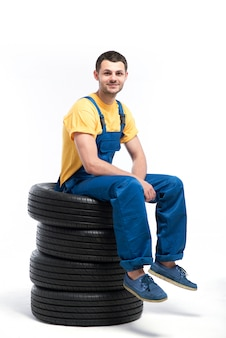 Il tecnico della gomma isolato su sfondo bianco, riparatore con pneumatici