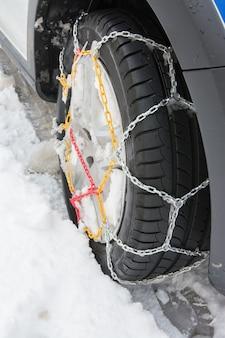 Pneumatico con catene da neve montate nel giorno di neve invernale