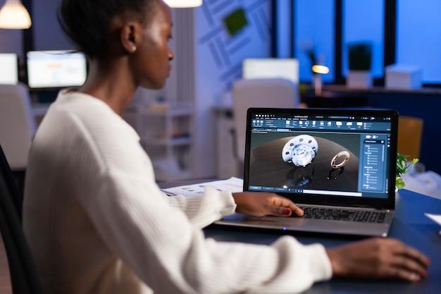 Ingegnere designer africano stanco che analizza un nuovo prototipo di modello 3d del prodotto industriale, facendo gli straordinari