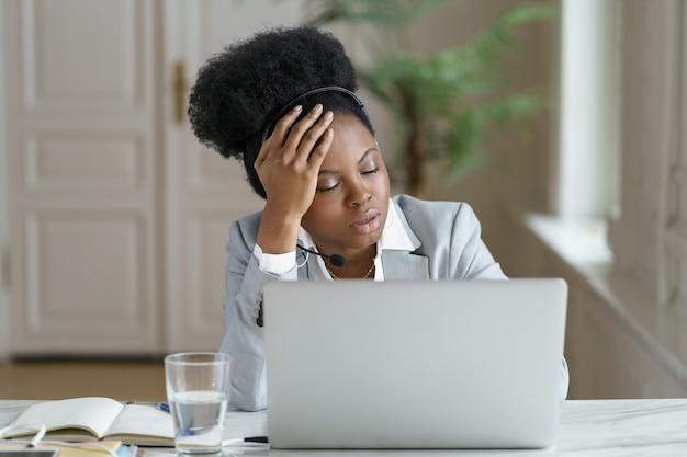 Impiegato d'ufficio afro stanco con le cuffie dorme sul posto di lavoro, affetto da stanchezza cronica