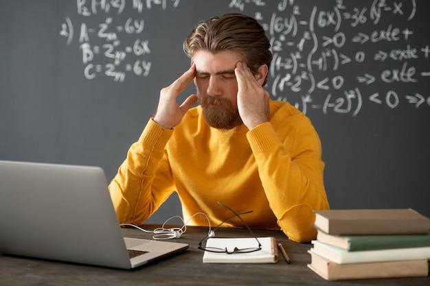 Insegnante di algebra stanco in abbigliamento casual che tocca il suo viso mentre si china sul tavolo davanti al computer portatile durante la lezione online contro la lavagna