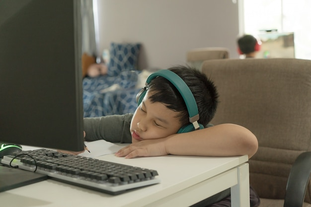 Stanco scolaretto asiatico si addormenta durante il corso di apprendimento online, noioso homeschooling durante la chiusura della scuola per l'epidemia di covid-19, schiacciando un pisolino, il ragazzo pigro non vuole finire i compiti.