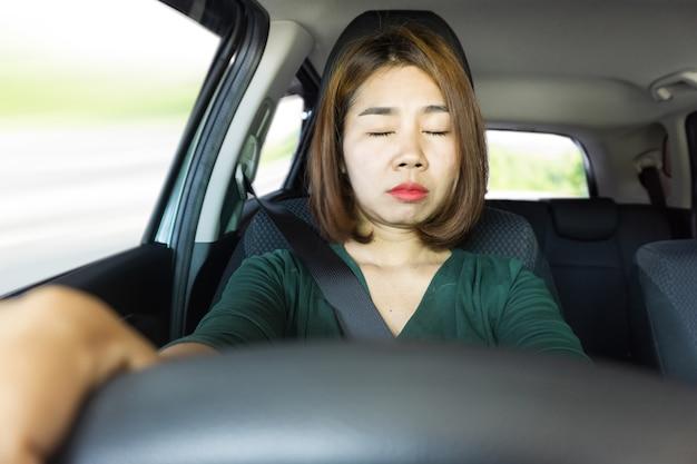 La donna asiatica stanca cade dormendo mentre guida l'auto