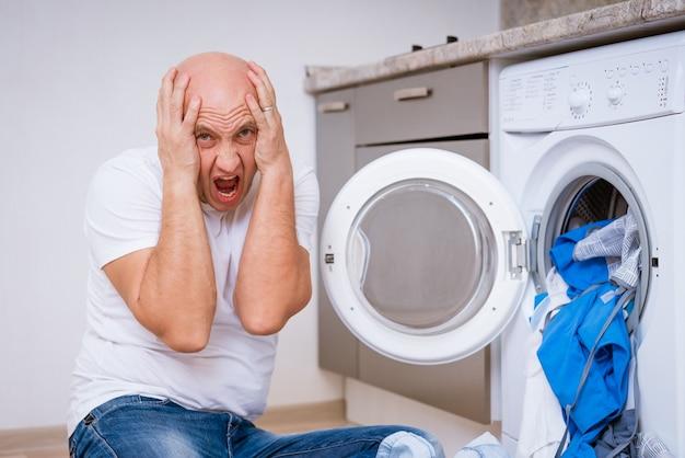 Uomo calvo stanco seduto con panni sporchi in lavatrice