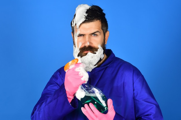 Uomo barbuto stanco con attrezzature per la pulizia. uomo con schiuma sulla testa. isolato su sfondo blu. uomo barbuto con spray detergente. concetto di pulizia. copia spazio per pubblicizzare l'impresa di pulizie.