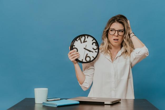 Bionda stanca in vetri che indossa camicia bianca che si siede al suo posto di lavoro con il computer portatile, la scadenza sta arrivando, lavoro annoiato