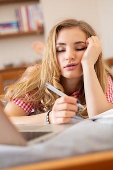 Studentessa bionda stanca che dorme durante una noiosa lezione online a casa a causa della pandemia globale di covid-19.