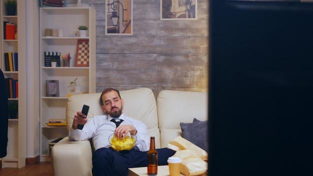 Uomo d'affari stanco e annoiato con cravatta che si rilassa guardando la tv mangiando patatine usando il telecomando.