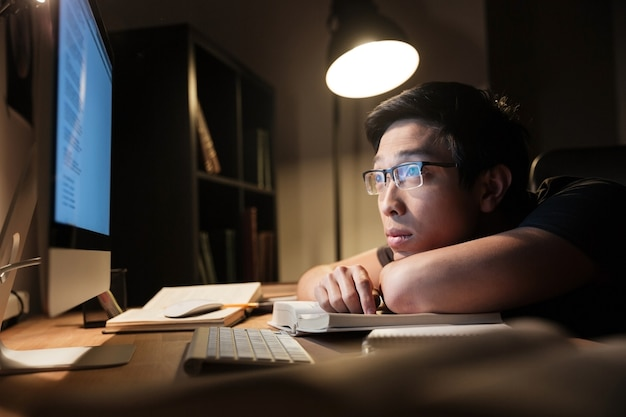 Stanco annoiato giovane con gli occhiali che studia usando libri e computer di notte